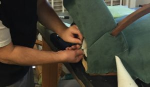 Team at work re-upholstering a sofa